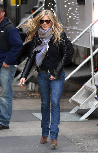 "A stylish Jennifer Aniston is all smiles as she leaves the set of the upcoming comedy ""Wanderlust"". The actress wore a black leather jacket, blue jeans, sunglasses, and a grey scarf."